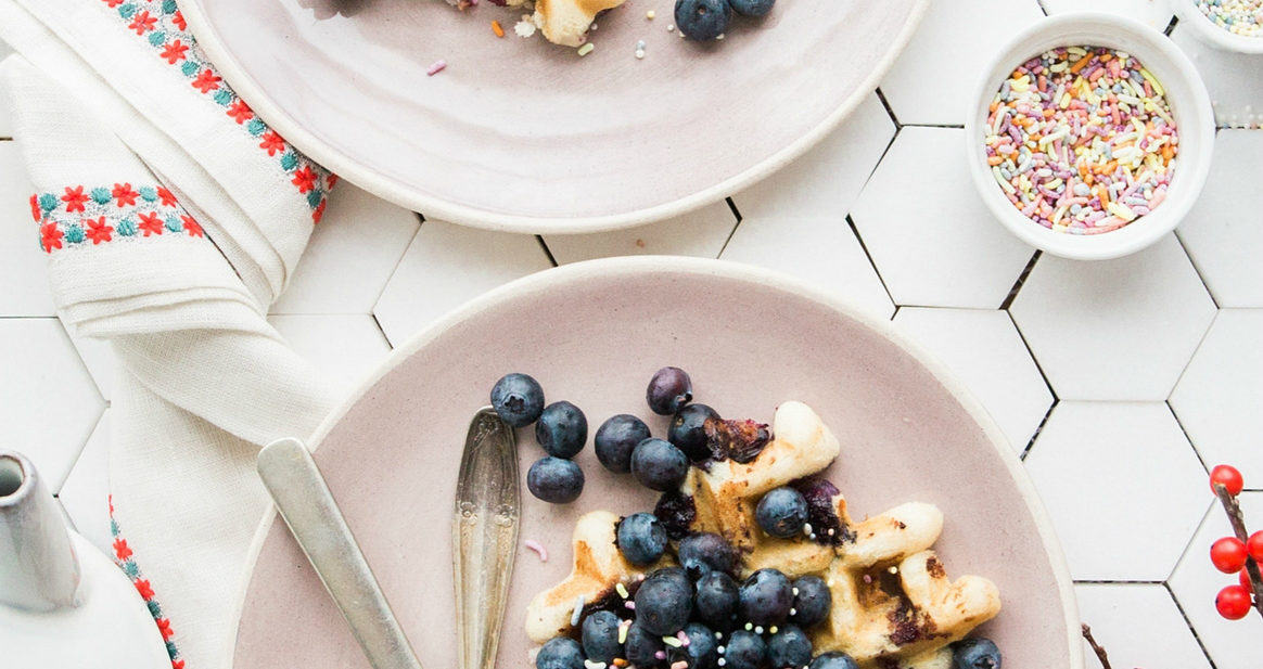 2 pink plates with blueberry waffles with sprinkles