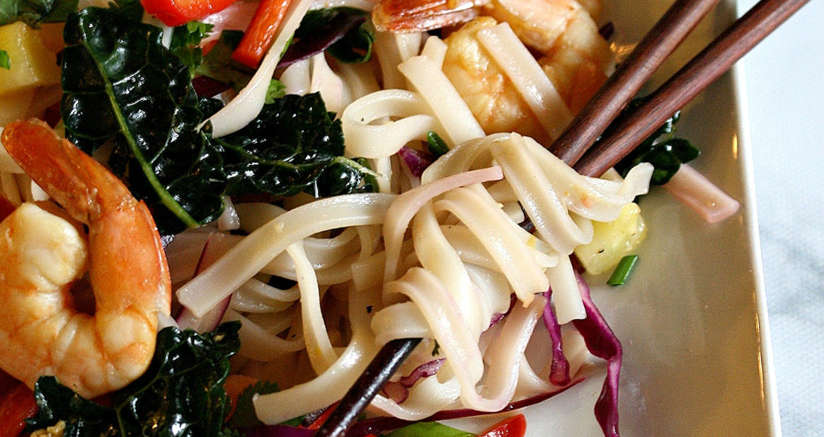 Plate with chopsticks in rice noodle salad with veggies and shrimp