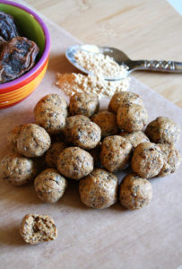 Cutting board with protein balls, maca powder, and dates