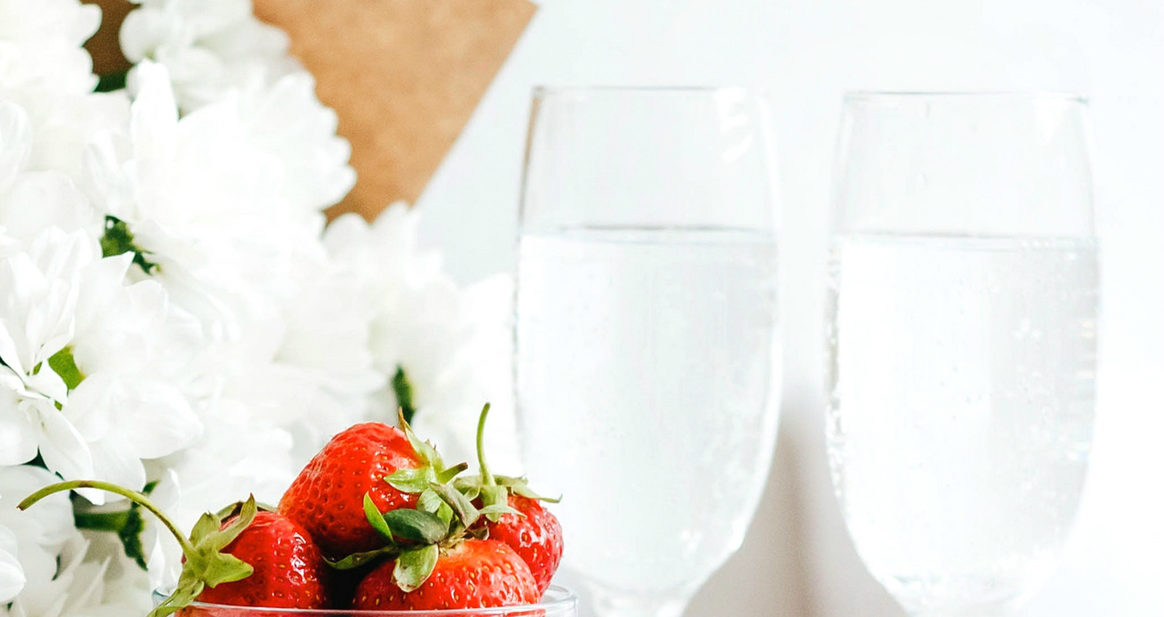 2 glasses of water with container of strawberries and fresh flowers