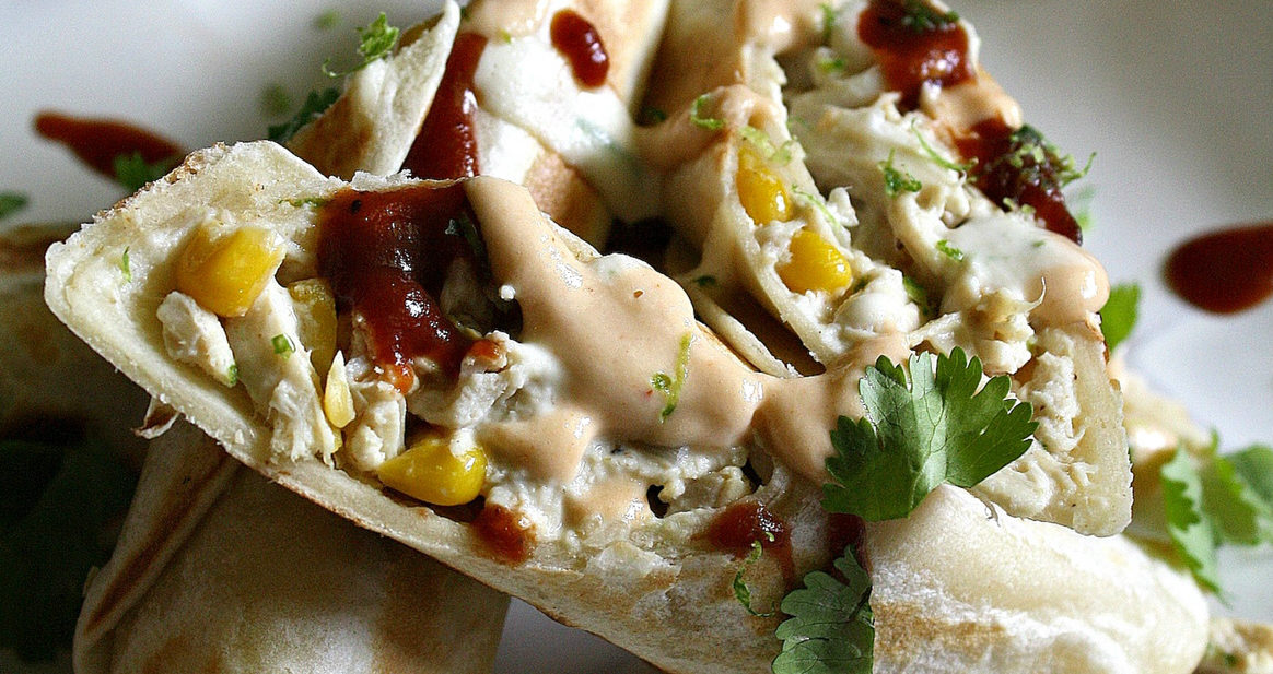 Plate with chicken and corn filled tortillas with lime, sriracha, dairy free cream cheese