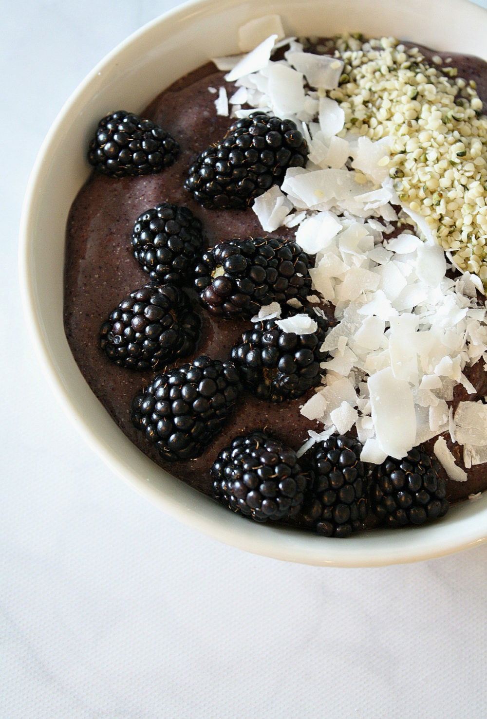White bowl filled with Blueberry Superfood Smoothie Bowl topped with blackberries, coconut chips, and hemp hearts