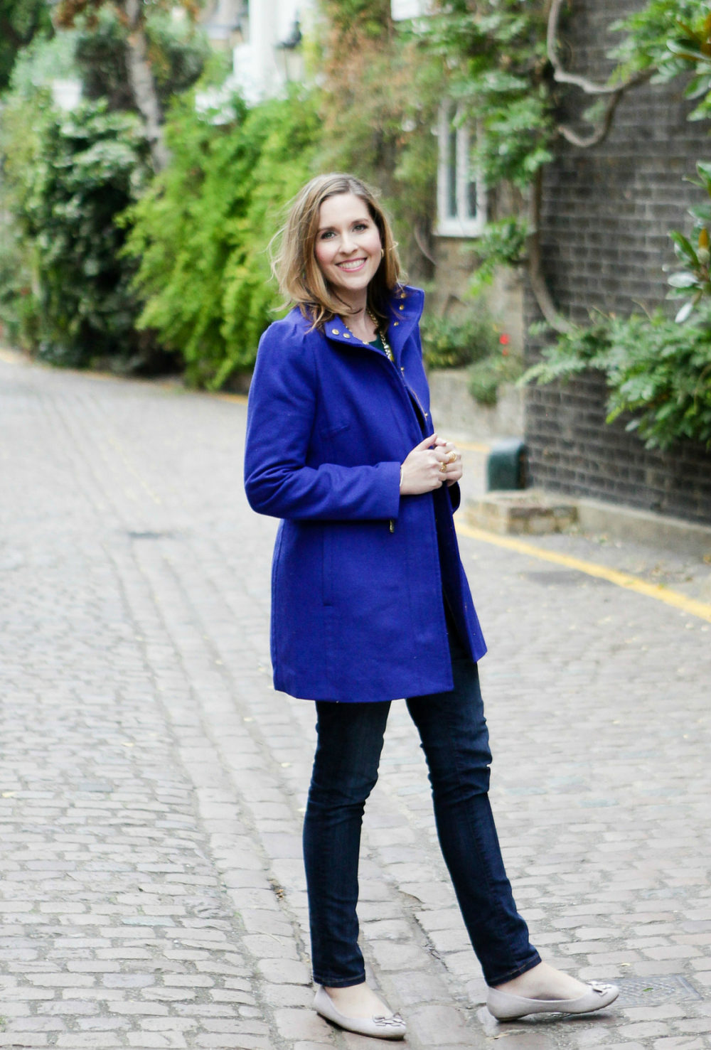 Girl standing in London mews in blue coat