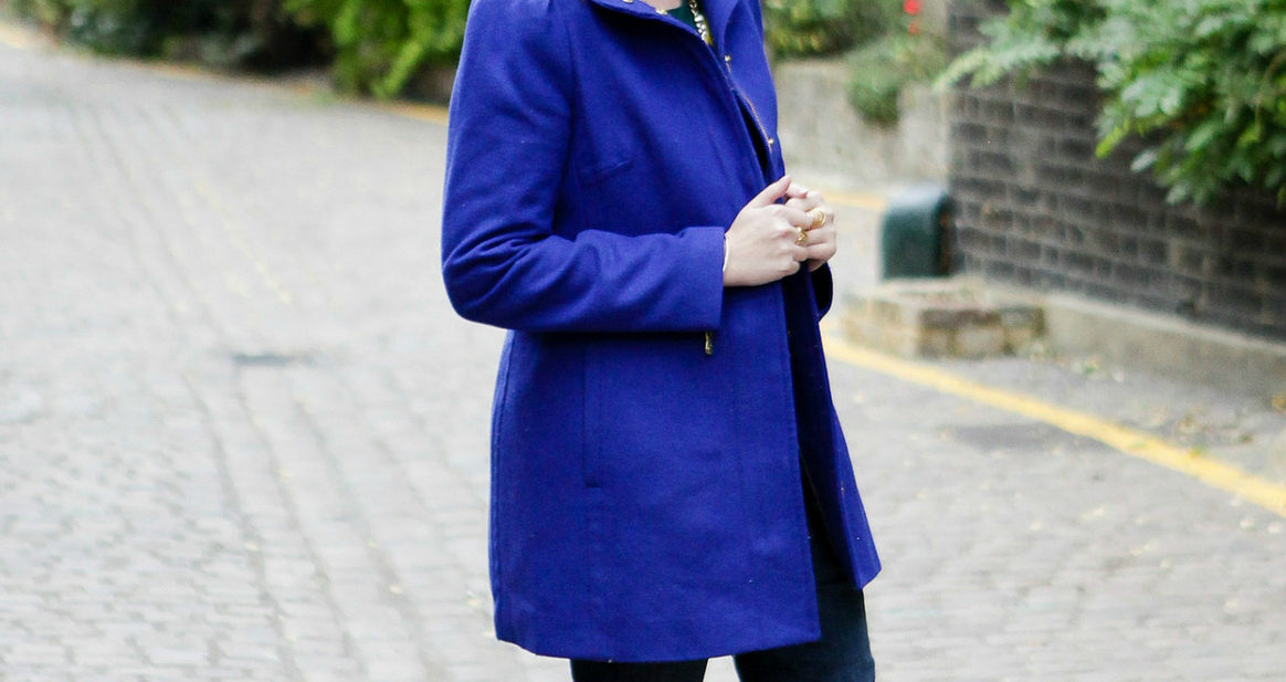 Girl standing in London mews in blue coat