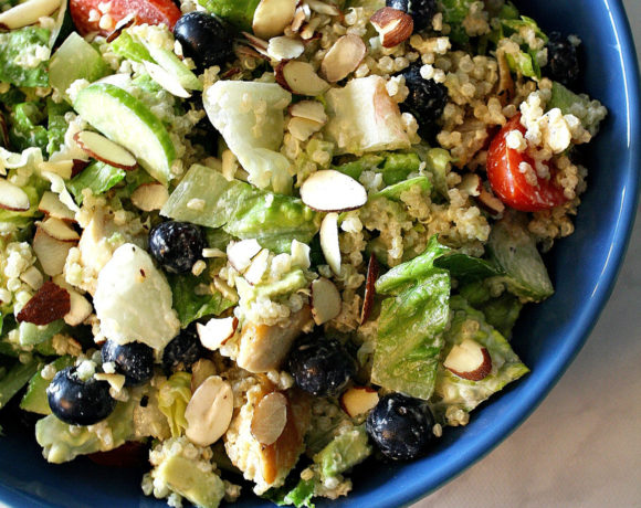 Bowl filled with dairy free salad including romaine lettuce, quinoa, blueberries, chicken, and almonds