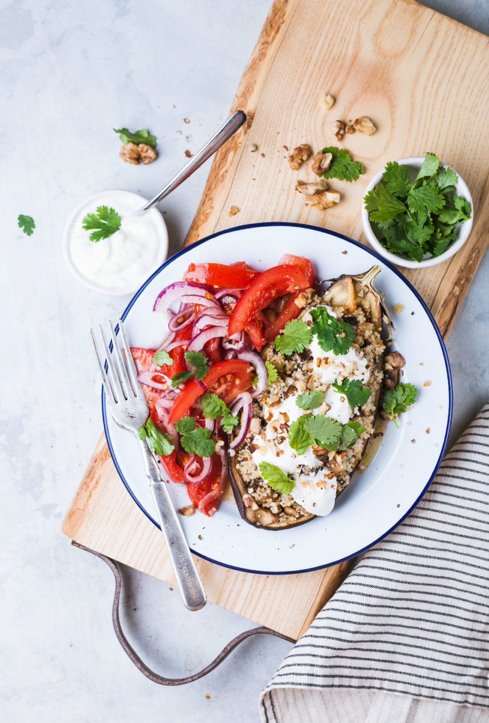 White plate on wood cutting board with tomato salad and eggplant meal
