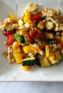 White plate with zucchini, yellow peppers, tomatoes, scrambled eggs, and basil
