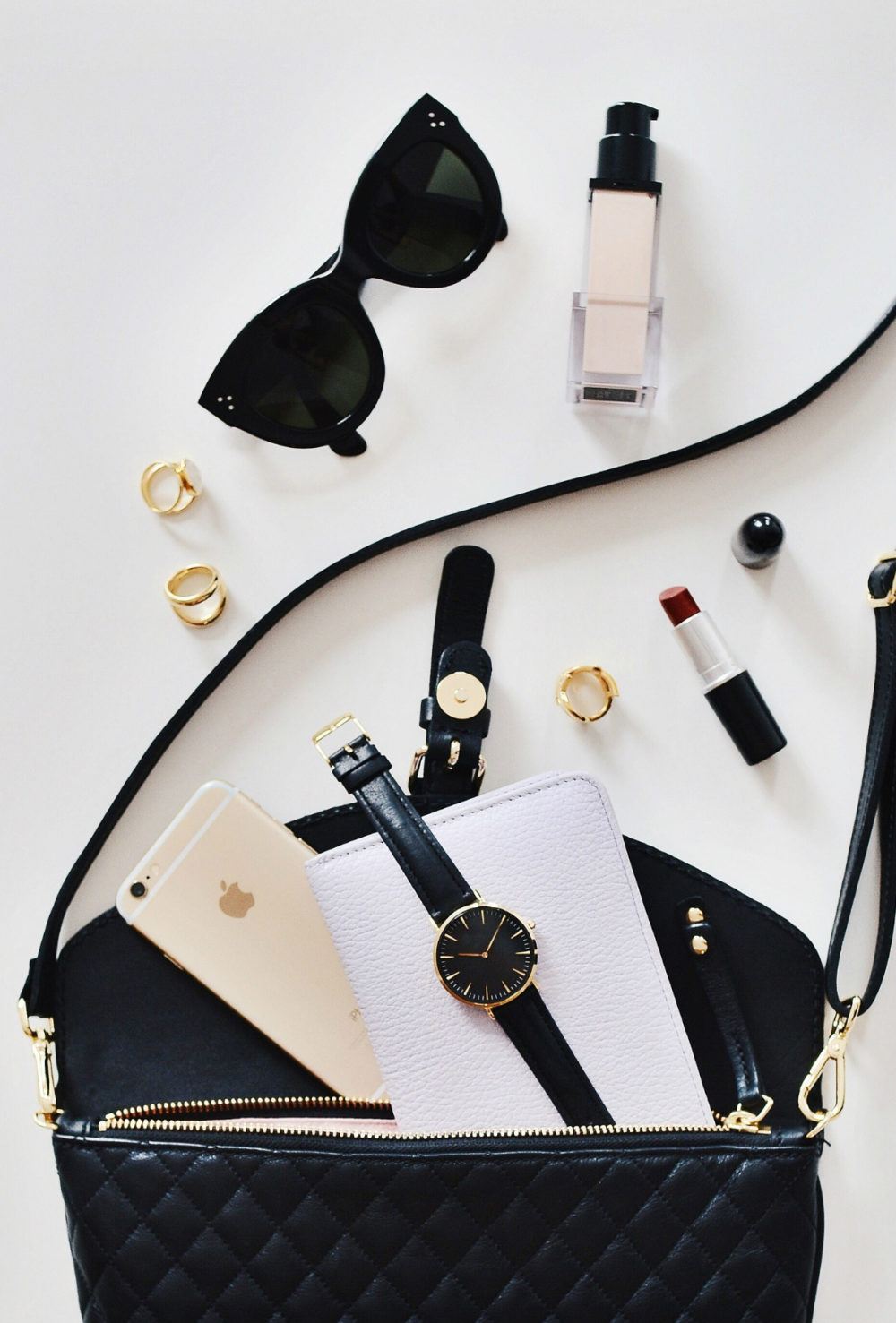 Black purse with sunglasses and cosmetics