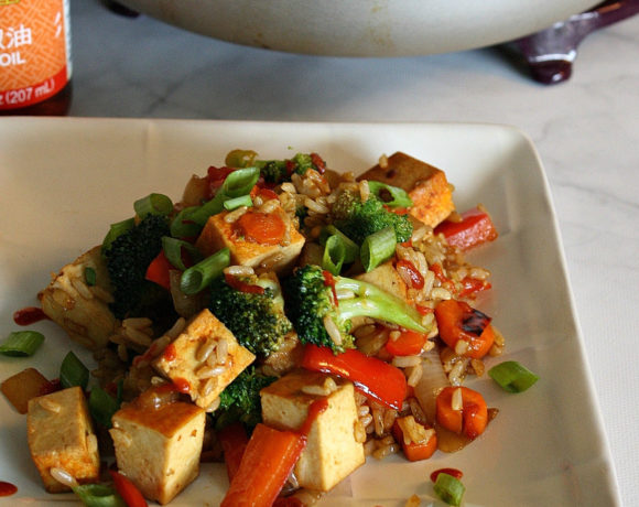 White plate on marble surface with stir fry vegetables and tofu