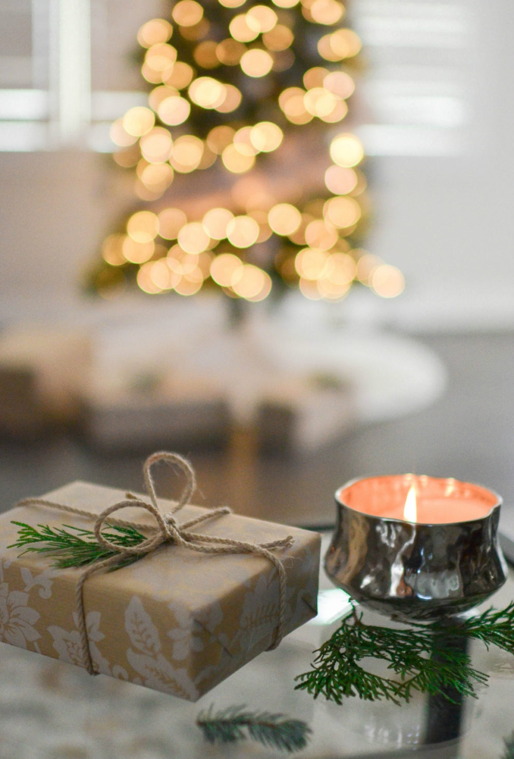 gift sitting on glass table with candle and Christmas tree