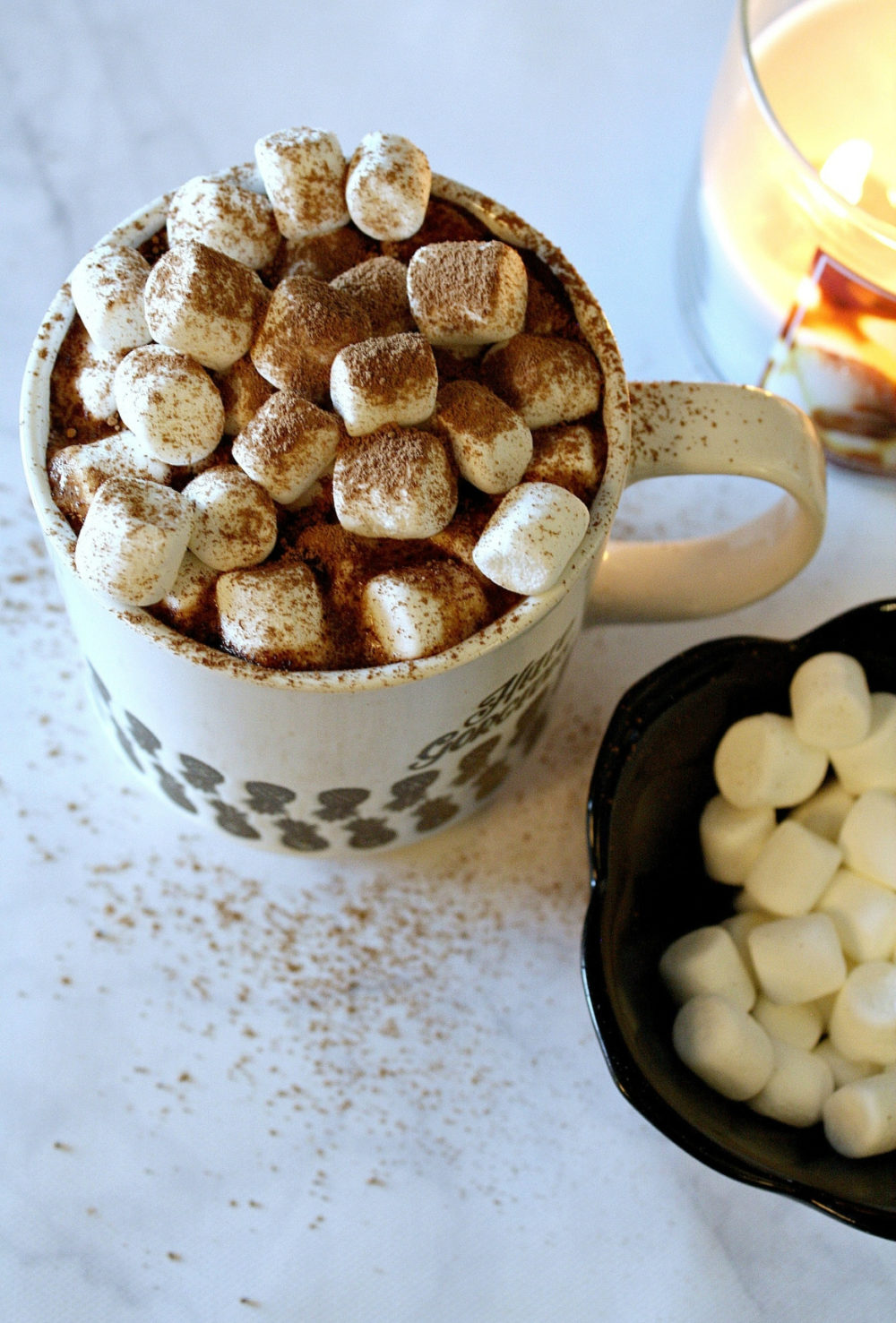 Mug with hot chocolate, marshmallows, and candle on white surface