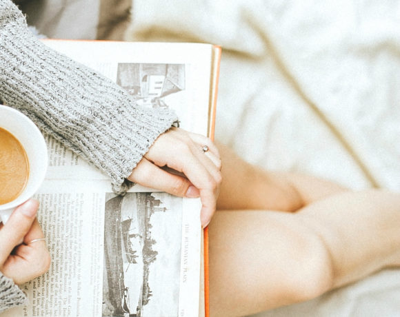 Woman sitting on white blanket reading with coffee